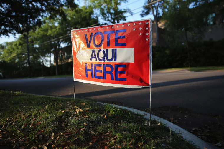 A bilingual sign stands outside a polling center at public library ahead of local elections on April 28, 2013 in Austin, Texas. (Photo by John Moore/Getty)