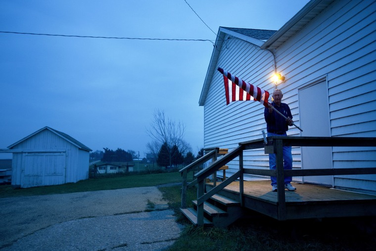 Election Inspector Jim Nodorft unfurls the American flag to hang it up outside the Smelser Town hall as the polls opened at 7 a.m. on November 6, 2012 in Georgetown, Wisconsin.