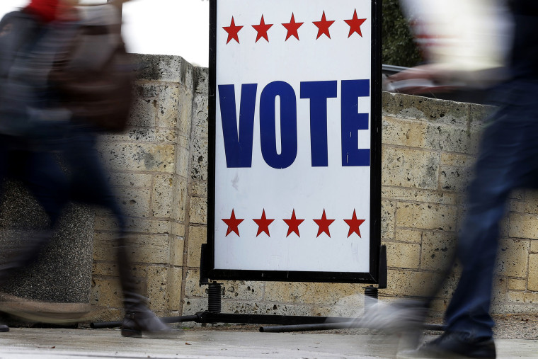 Pedestrians pass voting signs near an early voting polling site, in Austin, Texas.