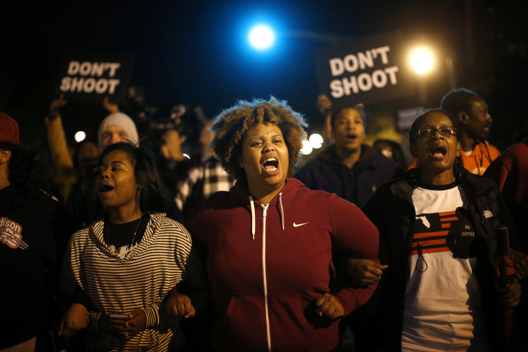 Protesters link arms after blocking an intersection after a vigil in St. Louis, Missouri, on Oct. 9, 2014.
