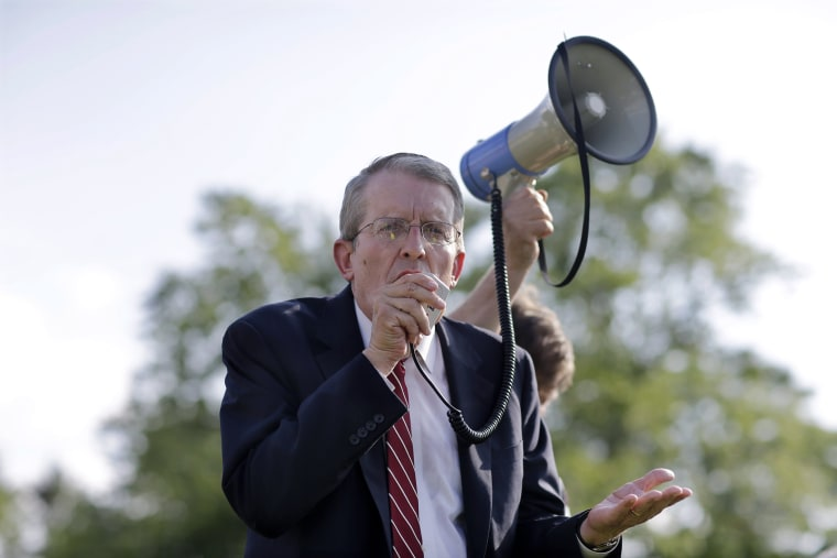 In this Monday, Aug. 4, 2014 photograph, Jeff Bell uses a bullhorn to address a gathering in Cherry Hill, N.J.