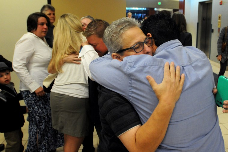 Jody May-Chang hugs her wife Maria May-Chang in the Ada County Courthouse Wednesday morning after copuples were denied a marriage license on Oct. 8, 2014 in Boise, Idaho. (Photo by Adam Eschbach/The Idaho Press-Tribune/AP)