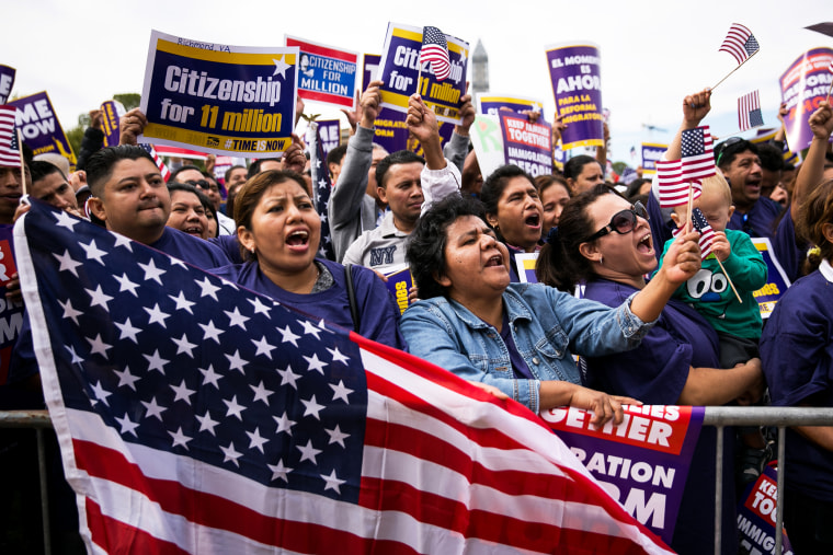 (L to R) Lorena Ramirez, of Arlington, Virginia, holds up an American flag as she cheers with her friend Lilia Beiec during a rally in support of immigration reform on October 8, 2013 in Washington, D.C. (Photo by Drew Angerer/Getty)