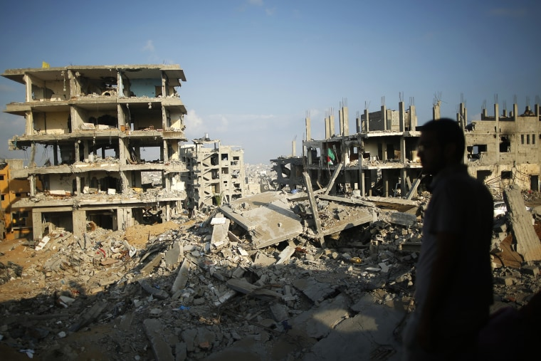 A Palestinian man stands atop the rubble of his house as he looks at the ruins of neighboring houses that witnesses said were destroyed or damaged during the 50-day war between the Hamas militant movement and Israel, in the east of Gaza City.