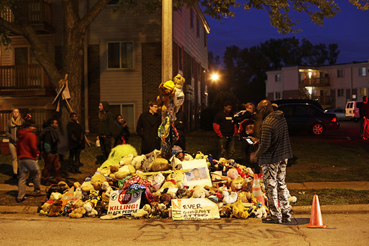 Demonstrators stand near a makeshift memorial for Michael Brown on Oct., 11 2014 in Ferguson, Mo. (Photo by Joshua Lott/AFP/Getty)