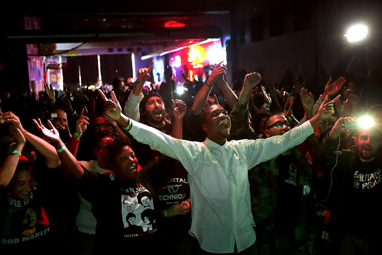 """Hip hop fans watch Talib Kweli during the \""""Hip Hop and Resistance\"""" concert at Fubar on Locust Street in St. Louis, Mo., on Oct. 12, 2014. (Robert Cohen/St. Louis Post-Dispatch/AP)"""