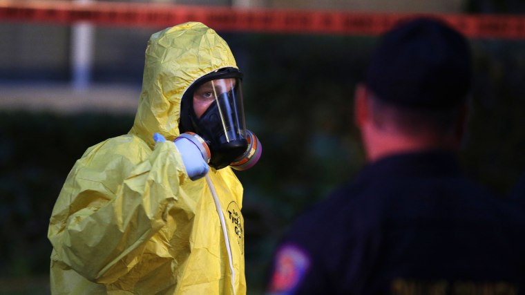 A hazmat worker looks up while finishing up cleaning outside an apartment building of a hospital worker, Oct. 12, 2014, in Dallas, Texas. (Photo by LM Otero/AP)