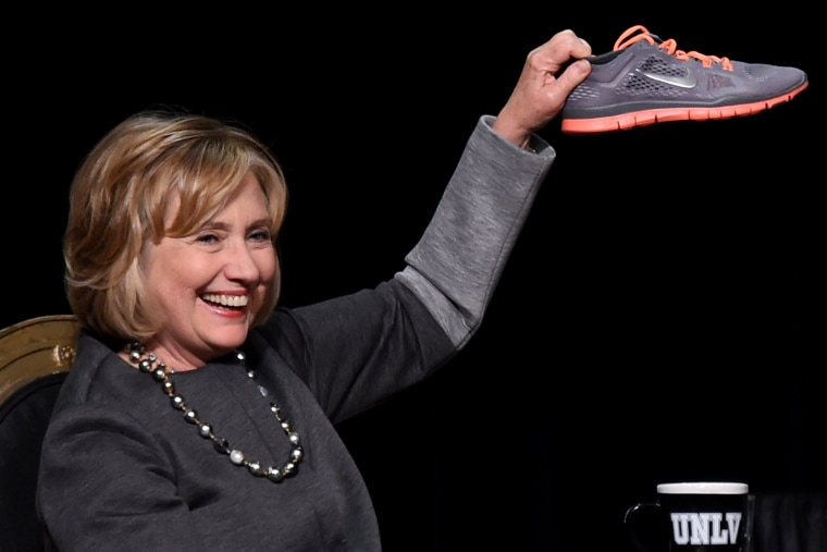 Former U.S. Secretary of State Hillary Clinton holds up a running shoe she received as a gift at a fundraising dinner for the UNLV Foundation at the Bellagio on Oct. 13, 2014 in Las Vegas.