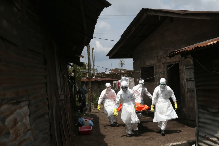 Ebola burial team members remove the body of Mekie Nagbe, 28, for cremation on Oct. 10, 2014 in Monrovia, Liberia.