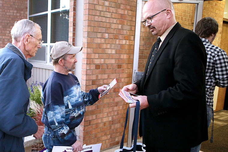 U.S. Senate candidate Dr. Doug Butzier, of Dubuque, right, hands out his campaign information in Davenport, Iowa on Oct. 11, 2014.