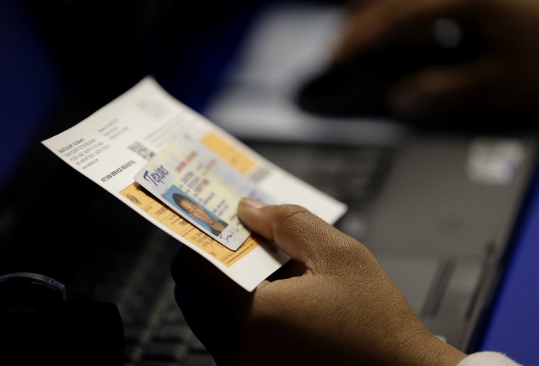 FILE - In this Feb. 26, 2014 file photo, an election official checks a voter's photo identification at an early voting polling site in Austin, Texas. A...