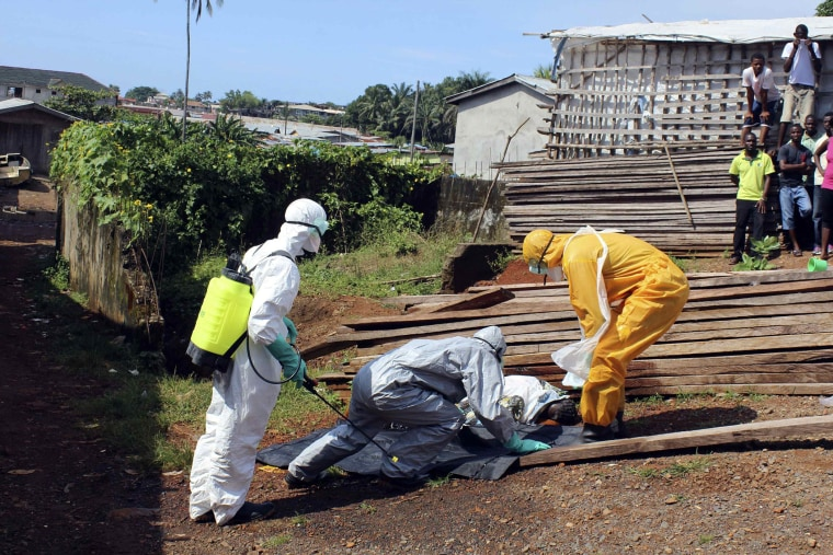 Health workers remove the body a woman who died from the Ebola virus in the Aberdeen district of Freetown, Sierra Leone on Oct. 14, 2014.