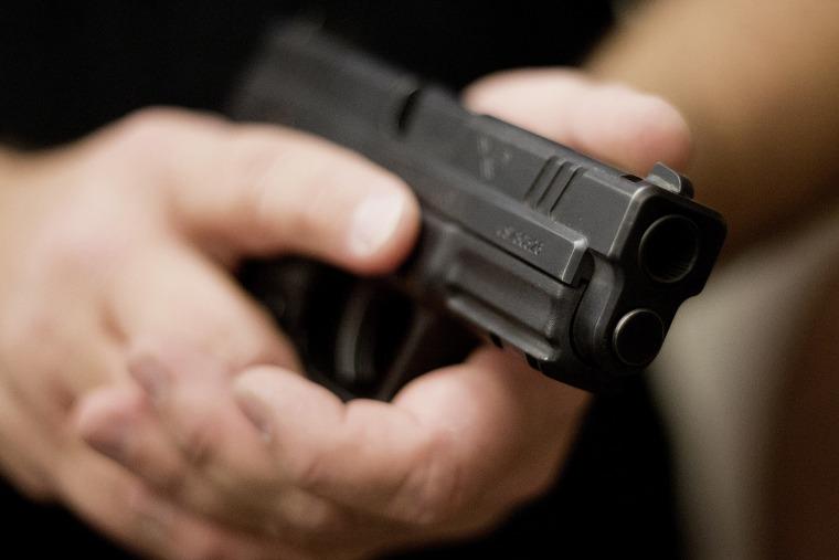 A firearms instructor holds a handgun.