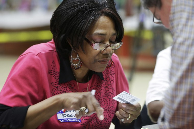 Election worker Dorothy Davis checks a voter's ID at a polling place in Little Rock, Ark. on May 20, 2014.