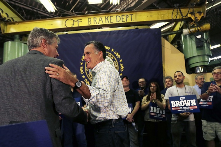 Former Republican Presidential candidate Mitt Romney gives New Hampshire Republican Senate candidate Scott Brown, left, a pat on the back during a campaign stop in Hudson, N.H. on Oct. 15, 2014.