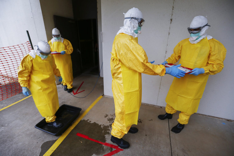 Students wearing personal protective equipment participate in a Centers for Disease Control and Prevention training session facility for healthcare workers treating Ebola virus victims in Anniston, Ala., on Oct. 15, 2014.