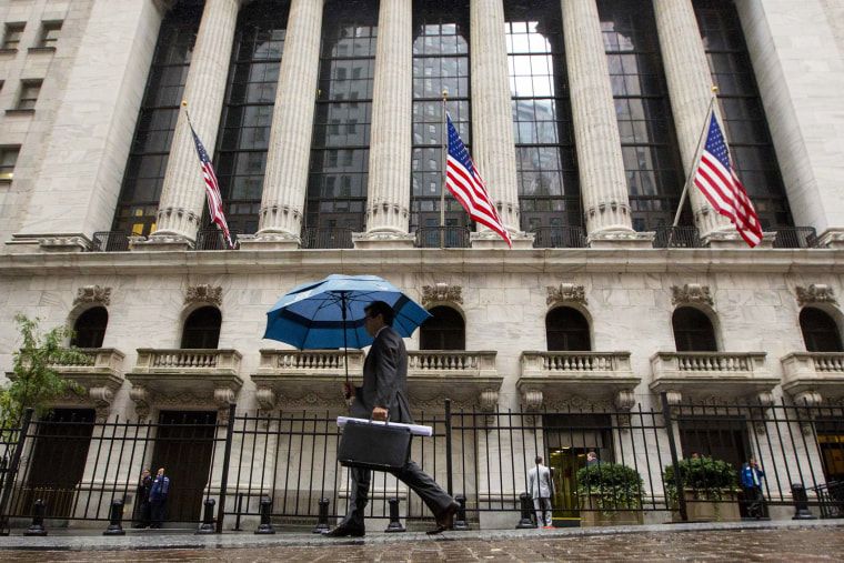 A man carries an umbrella in the rain as he passes the New York Stock Exchange on Oct. 16, 2014.