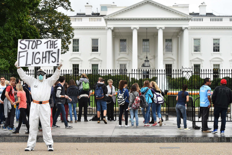 Jeff Hulbert from Annapolis, Md., dressed in a protective suit and mask, holds a poster demanding for a halt of all flights from West Africa as he protests outside the White House in Washington, D.C. on Oct. 16, 2014.