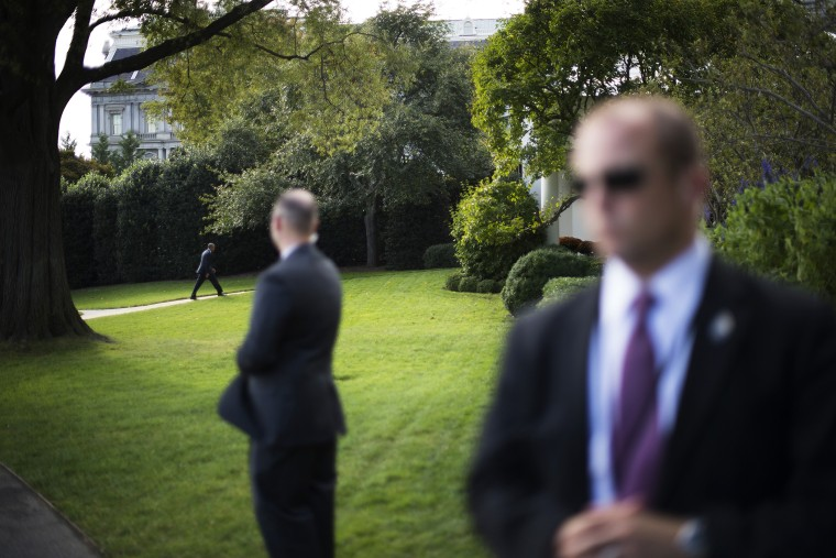US Secret Service officers stand watch as US President Barack Obama returns to the Oval Office at the White House in Washington, D.C., Oct. 14, 2014. (Photo by Jim Watson/AFP/Getty)