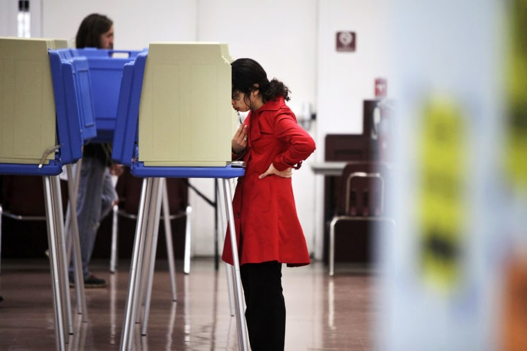 Wendy Mena, 18, studies her choices as she votes in her first election in Cary, N.C. on Nov. 6, 2012.