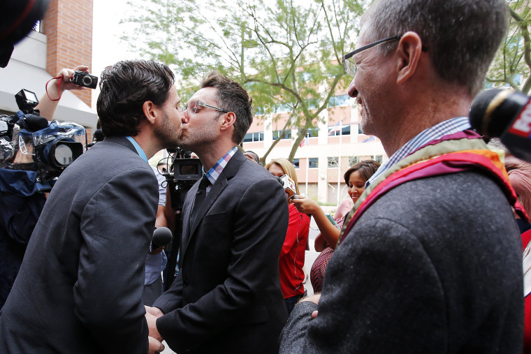 Kevin Patterson, left, and David Larance kiss after exchanging vows, as Rev. John Dorhaer, who performed the ceremony, stands at right, on Oct. 17, 2014, in Phoenix, Ariz.