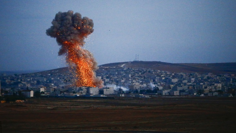 Smoke rises over Syrian town of Kobani after an airstrike, as seen from the Mursitpinar border crossing on the Turkish-Syrian border in the southeastern town of Suruc, Turkey on Oct. 18, 2014. (Photo by Kai Pfaffenbach/Reuters)