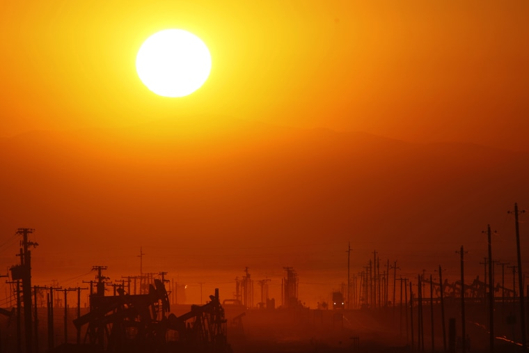 The sun rises over an oil field over the Monterey Shale formation where gas and oil extraction using hydraulic fracturing, or fracking, is on the verge of a boom on March 24, 2014 near Lost Hills, Calif. (Photo by David McNew/Getty)