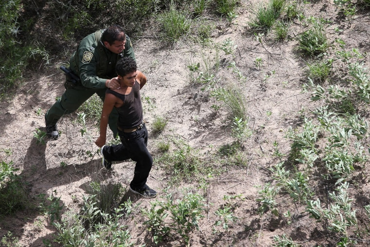 A U.S. Border Patrol agent detains an undocumented immigrant who fled from agents through dense brush on Sept. 9, 2014 near Falfurrias, Texas.