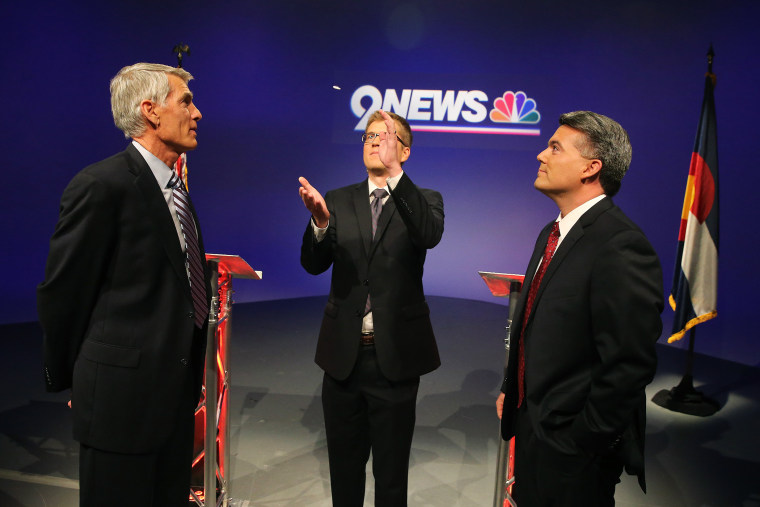Incumbent Democratic Sen. Mark Udall, and his opponent U.S. Rep. Cory Gardner, right, watching a coin flip by moderator Brandon Rittiman to see who gets first question during their final pre-election televised debate in Denver. Colo. on Oct. 15, 2014.