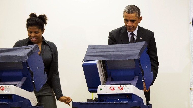 President Barack Obama votes next to Aia Cooper at the Dr. Martin Luther King Community Service Center in Chicago, Ill. on Oct. 20, 2014.