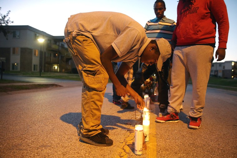 Neighborhood residents light candles at a memorial for 18-year-old Michael Brown on Canfield Street on Oct. 20, 2014 in Ferguson, Mo.