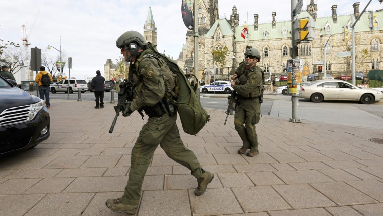 Armed RCMP officers head towards the Langevin Block on Parliament Hilll following a shooting incident in Ottawa on Oct. 22, 2014. (Chris Wattie/Reuters)