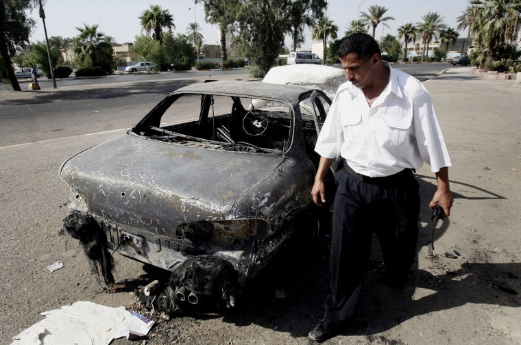 In this Sept. 25, 2007 file photo, an Iraqi traffic policeman inspects a car destroyed by a Blackwater security detail in al-Nisoor Square in Baghdad, Iraq. (Khalid Mohammed/AP)