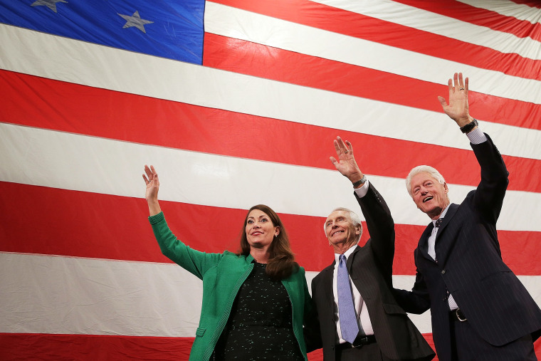 Former U.S. President Bill Clinton (R) campaigns for U.S. Senate Democratic candidate and Kentucky Secretary of State Alison Lundergan Grimes (L) with Kentucky Gov. Steve Beshear (C) during a rally on Oct. 21, 2014 in Paducah, Ky.