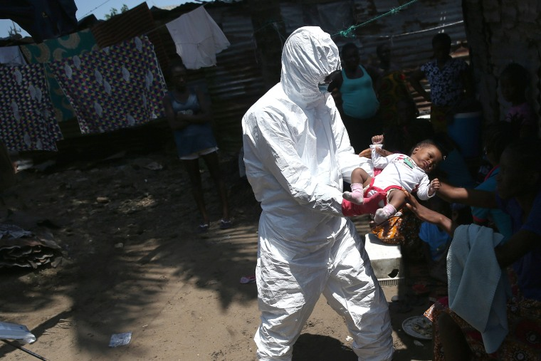 A health worker takes Benson, 2 months, from his mother to carry him to a re-opened Ebola holding center in the West Point neighborhood on Oct. 17, 2014 in Monrovia, Liberia. (John Moore/Getty)