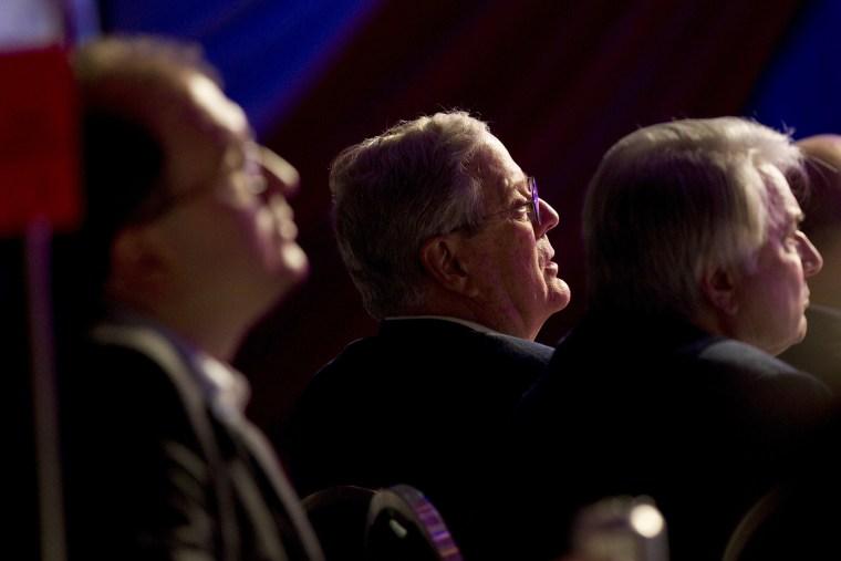 David Koch listens to Mitt Romney speak in Washington on Nov. 4, 2011.