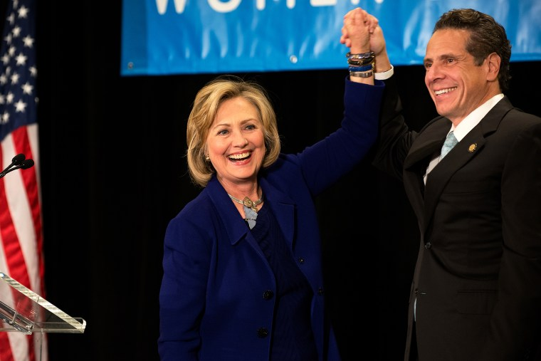 """Former U.S. Secretary of State and U.S. Sen. Hillary Rodham Clinton (left) raises the hand of incumbent New York Governor Andrew Cuomo (right) laugh during a \""""Women for Cuomo\"""" campaign event on Oct. 23, 2014 in New York, NY. (Photo by Bryan Thomas/Getty)"""