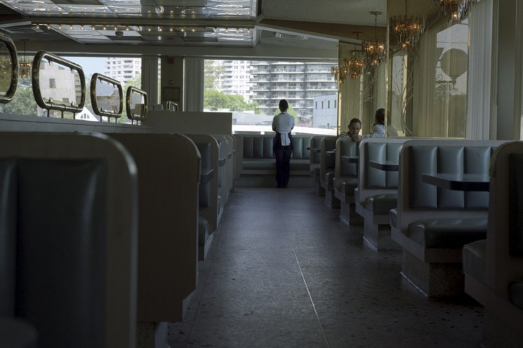 A waitress looks out the window of a diner in Fort Lee, N.J. (Photo by Kelly Shimoda/Redux)
