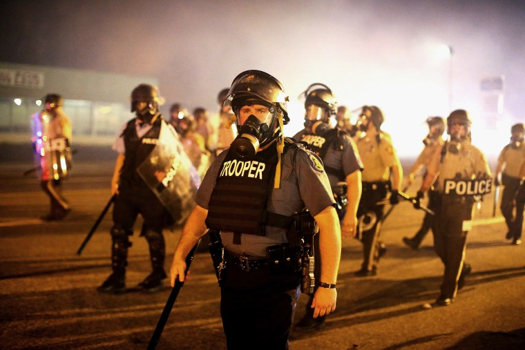 Police advance through a cloud of tear gas toward demonstrators protesting the killing of teenager Michael Brown on Aug. 17, 2014 in Ferguson, Mo.