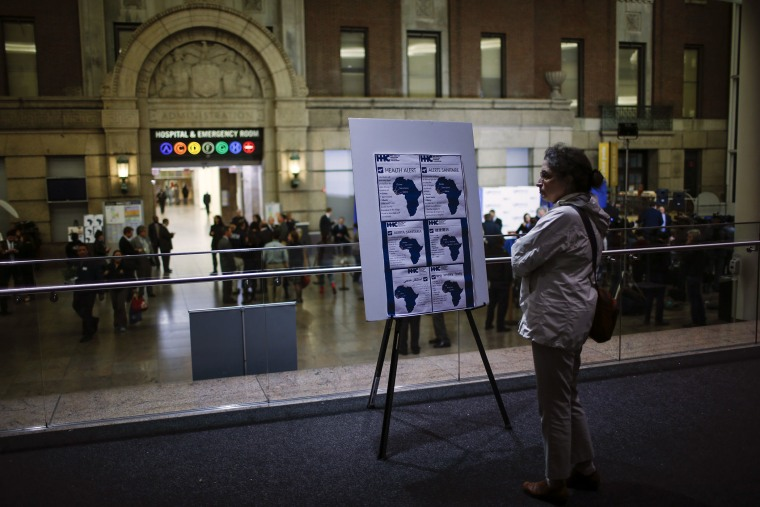 A woman reads alert on Ebola inside the Bellevue Hospital where Dr. Craig Spencer is being treated for Ebola symptoms in New York on Oct. 23, 2014.