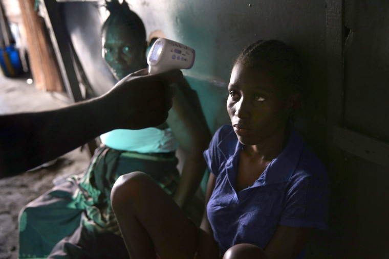 An Ebola tracing coordinator checks the temperature of Jessica Sompon, 17, finding her to have a fever in the West Point neighborhood on October 17, 2014 in Monrovia, Liberia.