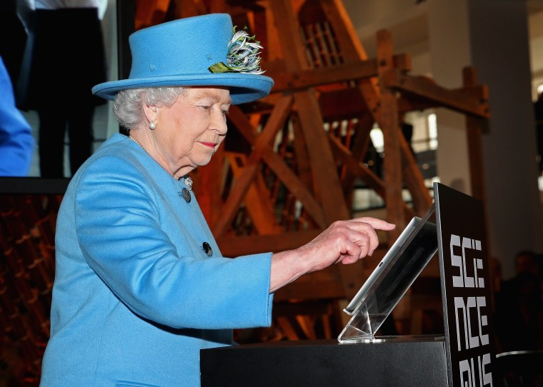 Britain's Queen Elizabeth II sends her first tweet during a visit to open the 'Information Age' exhibition at the Science Museum in London on Oct. 24, 2014.