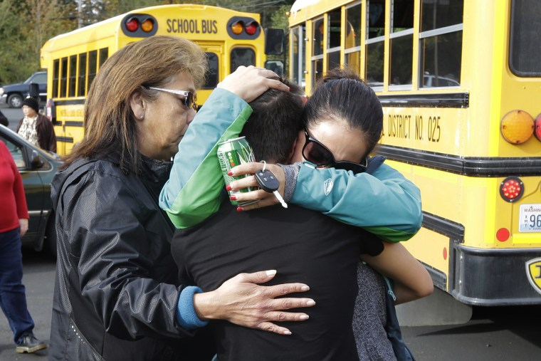 People embrace in front of school busses at a church, Oct. 24, 2014, where students were taken to be reunited with parents following a shooting at Marysville Pilchuck High School in Marysville, Wash. (Photo by Ted S. Warren/AP)