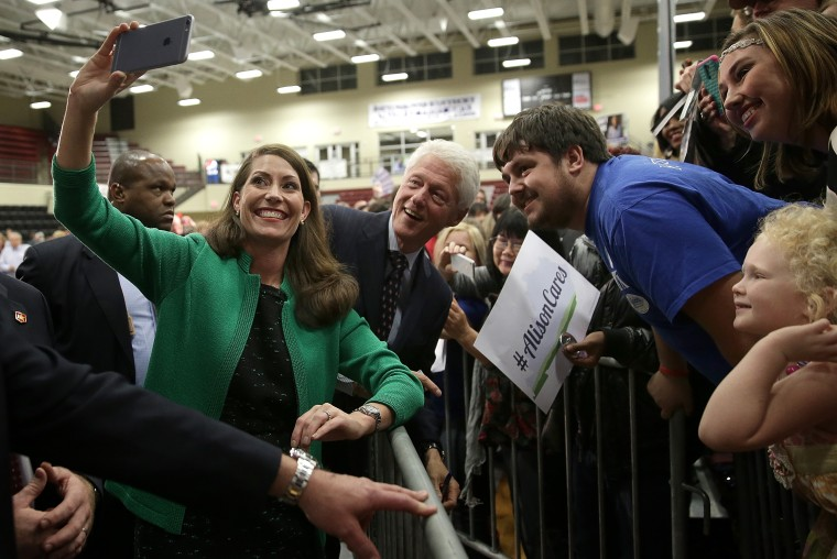 """Former U.S. President Bill Clinton (C) and U.S. Senate Democratic candidate and Kentucky Secretary of State Alison Lundergan Grimes (L) take a \""""selfie\"""" with Kentucky voters after they spoke at a rally Oct. 21, 2014 in Paducah, Ky."""