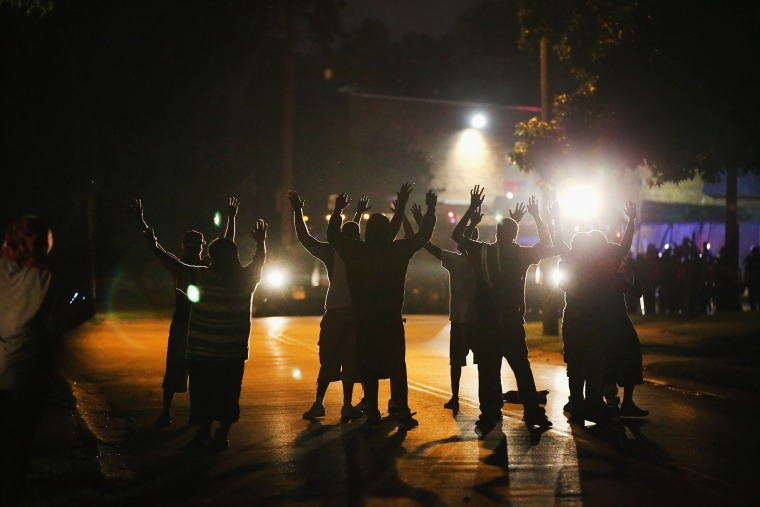 With their hands raised, residents gather in protest at a police line in Ferguson, Mo. on Aug. 11, 2014.