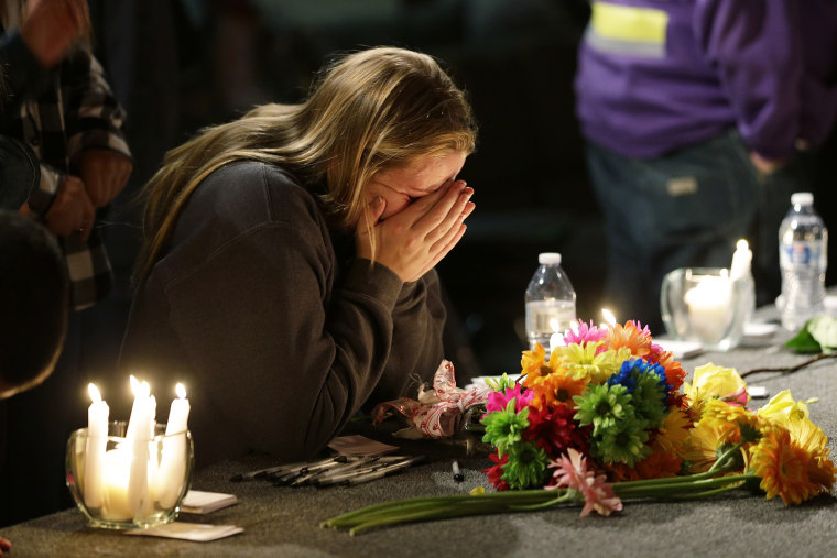 A young woman holds her head in her hands as she kneels before candles and flowers placed on the stage at the Grove Church in Marysville, Wash., Oct. 24, 2014, after a memorial vigil held for people affected by a shooting at Marysville Pilchuck High Schoo