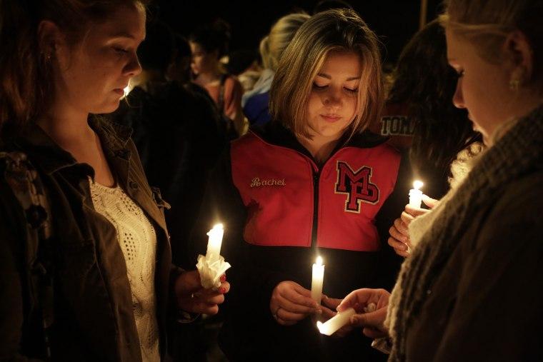 Katelynn Janisko (L-R), 15, Rachel Cowan, 15, and Jamison Strickland, 15, light candles at a vigil after a shooting at Marysville-Pilchuck High School in Marysville, Wash., Oct. 24, 2014. (Photo by Jason Redmond/Reuters)