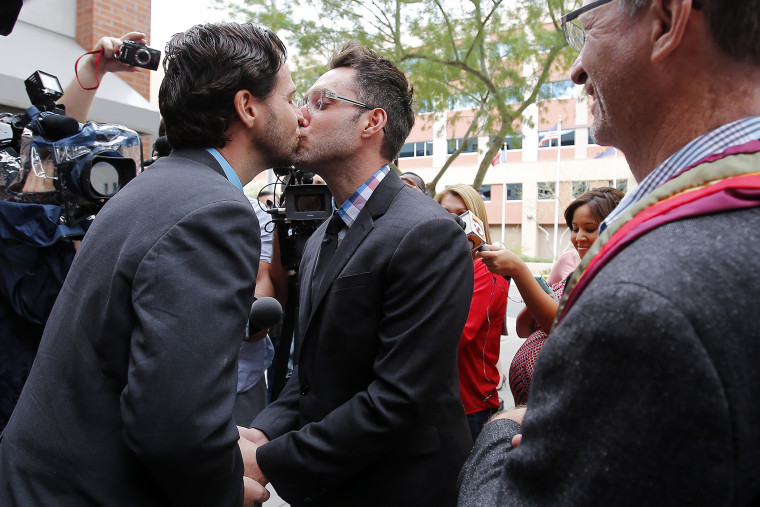 Kevin Patterson, left, and David Larance kiss after exchanging vows, as Rev. John Dorhaer, who performed the ceremony, stands at right, Oct. 17, 2014, in Phoenix, Ariz. (Photo by Rick Scuteri/AP)