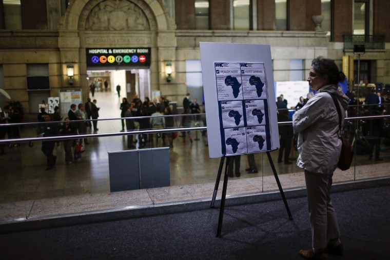 A woman reads alert on Ebola inside the Bellevue Hospital where Dr. Craig Spencer is being treated for Ebola symptoms in New York, N.Y., on Oct. 23, 2014. (Photo by Eduardo Munoz/Reuters)