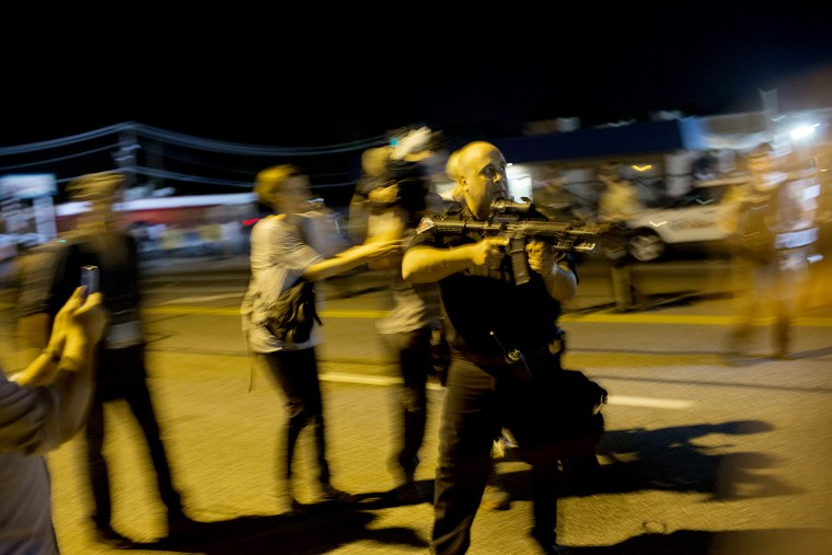 St. Ann, Missouri police officer Lt. Ray Albers points an assault rifle during a protest of the death of teenager Michael Brown on Aug. 19, 2014 in Ferguson, Mo.